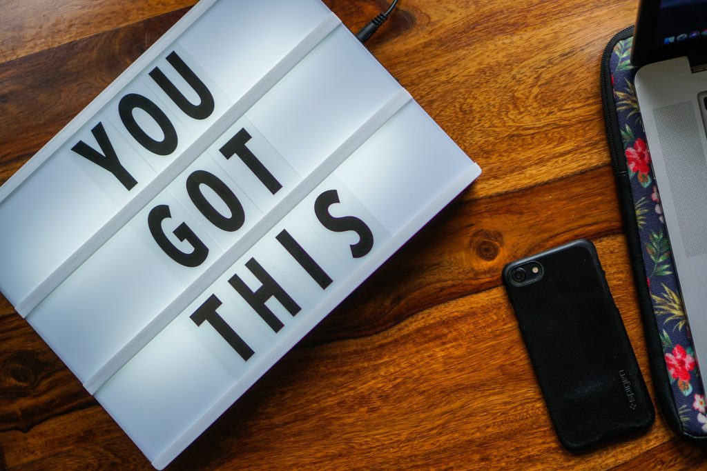 A lightbox with the phrase 'You Got This' on a desk with a mobile phone