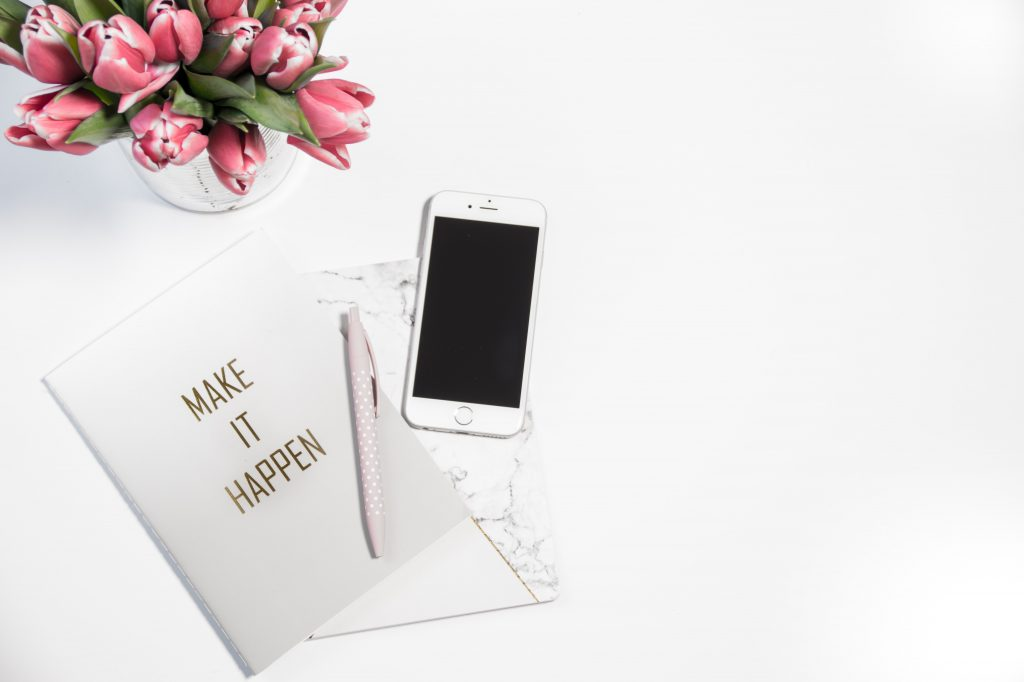 'Make it Happen' Notepad with a pen and a phone next to a vase with pink tulips